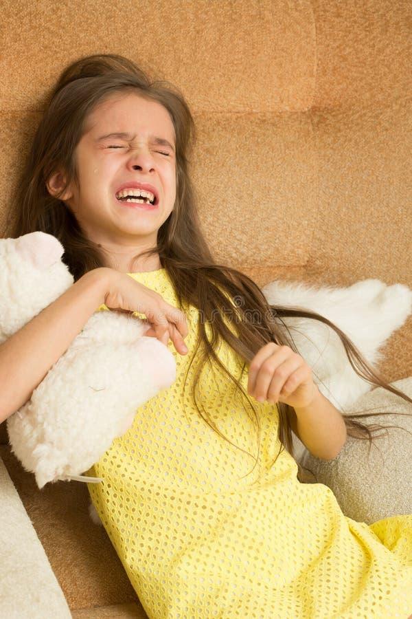Kleines Mädchen, das auf einem Stuhl schreit lizenzfreies stockfoto