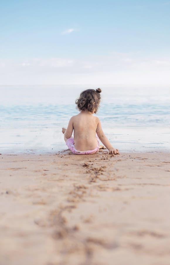 Kleines Mädchen, das auf einem tropischen Strand spielt stockfoto