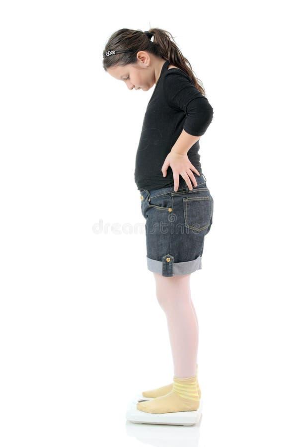 Kleines Mädchen, das auf einer Gewichtskala steht lizenzfreie stockfotografie