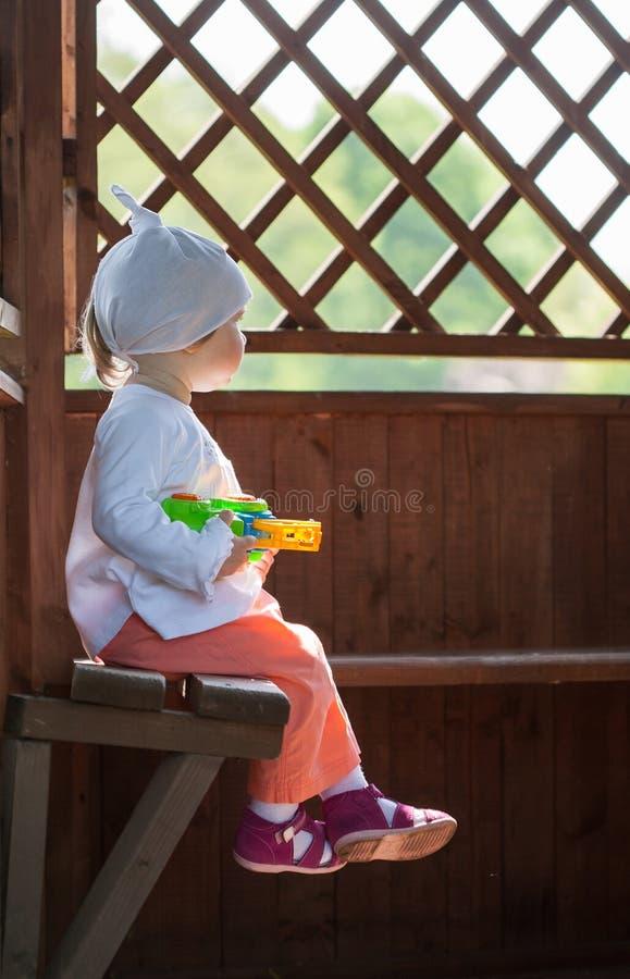 Kleines Mädchen, das auf einer Holzbank sitzt lizenzfreie stockfotografie