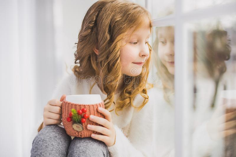 Kleines Mädchen, das auf Fensterbrett, trinkender heißer Tee sitzt lizenzfreies stockfoto