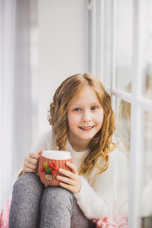 Kleines Mädchen, das auf Fensterbrett, trinkender heißer Tee sitzt stockbild