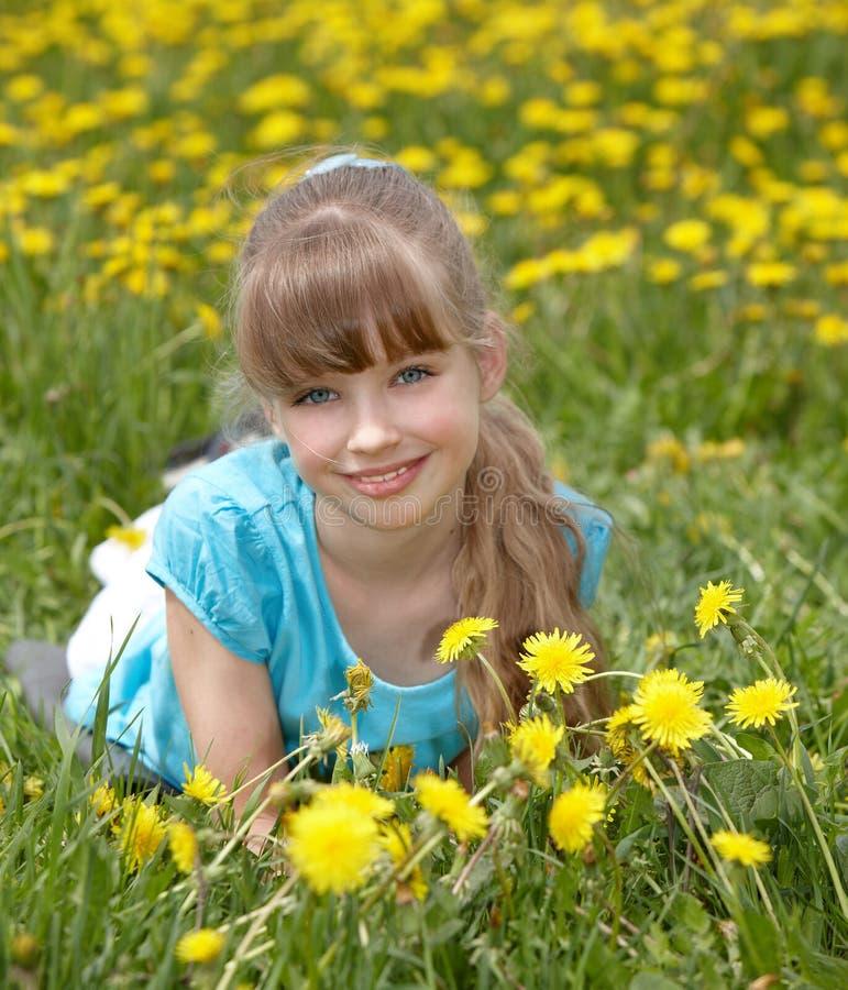 Kleines Mädchen, das auf Gras in der Blume liegt. lizenzfreies stockfoto