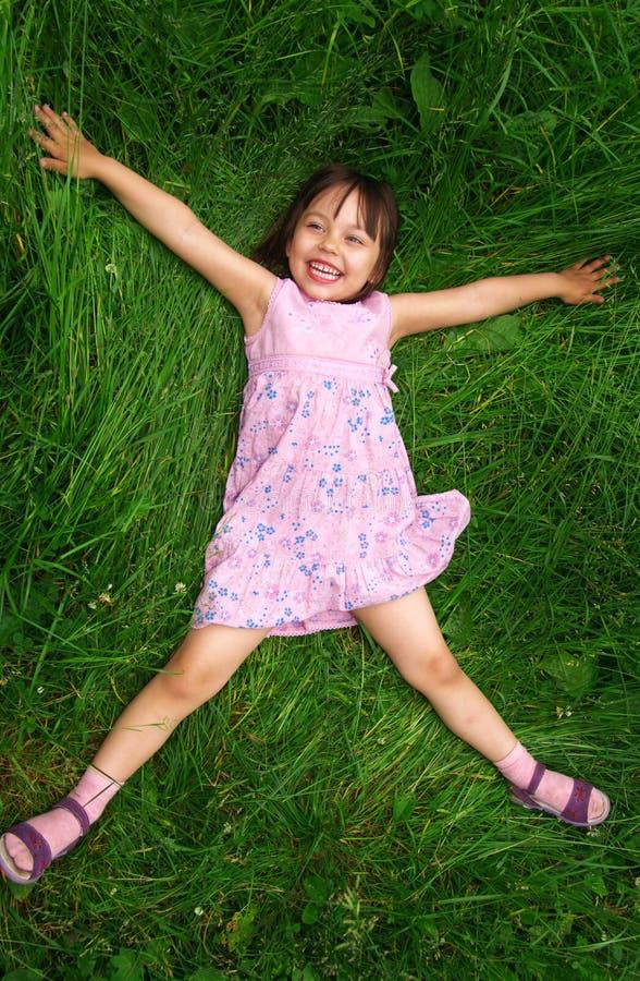 Kleines Mädchen, das auf Gras liegt stockbilder