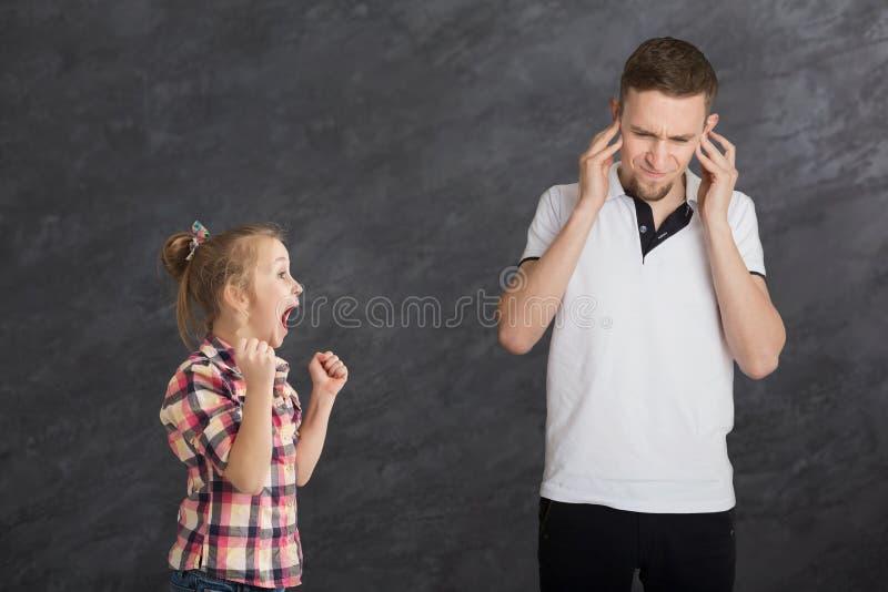 Kleines Mädchen, das auf ihrem älteren Bruder schreit lizenzfreie stockbilder