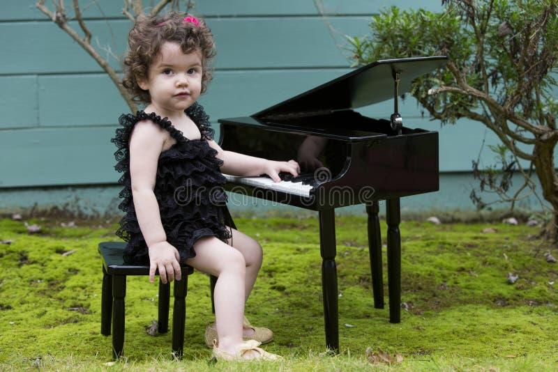 Kleines Mädchen, das auf Spielzeugklavier spielt stockbild