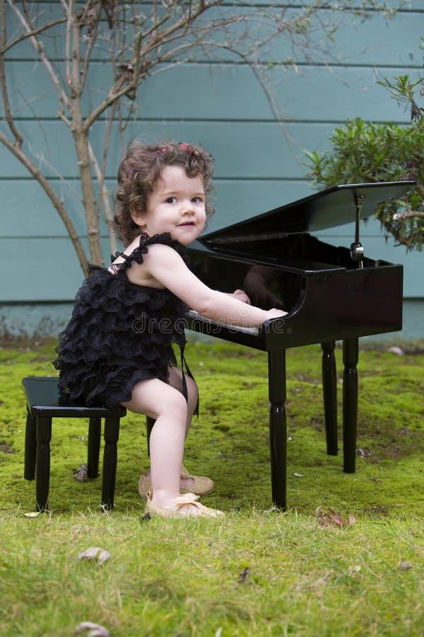 Kleines Mädchen, das auf Spielzeugklavier spielt lizenzfreies stockfoto