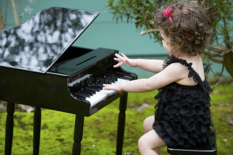 Kleines Mädchen, das auf Spielzeugklavier spielt stockfotografie