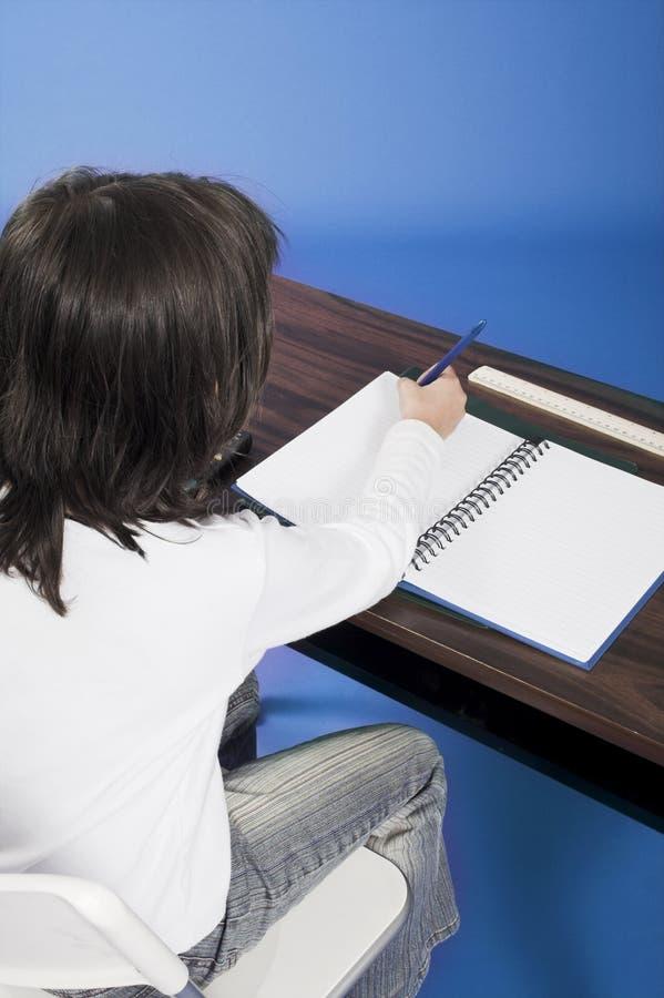 Kleines Mädchen, das auf Stuhl im Klassenzimmer sitzt lizenzfreie stockfotografie