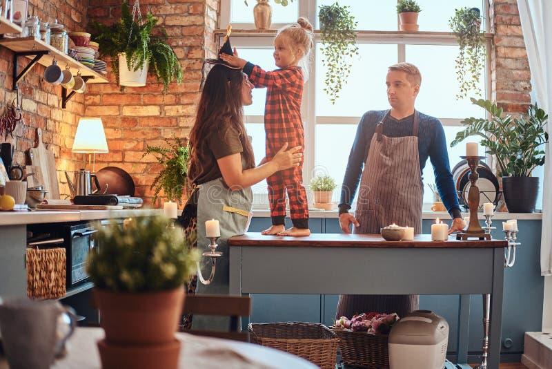 Kleines Mädchen, das auf Tabelle stehen und Kleider, die ein magischer Hut auf ihrer Mutter in der Dachbodenartküche am Morgen vo lizenzfreie stockfotografie