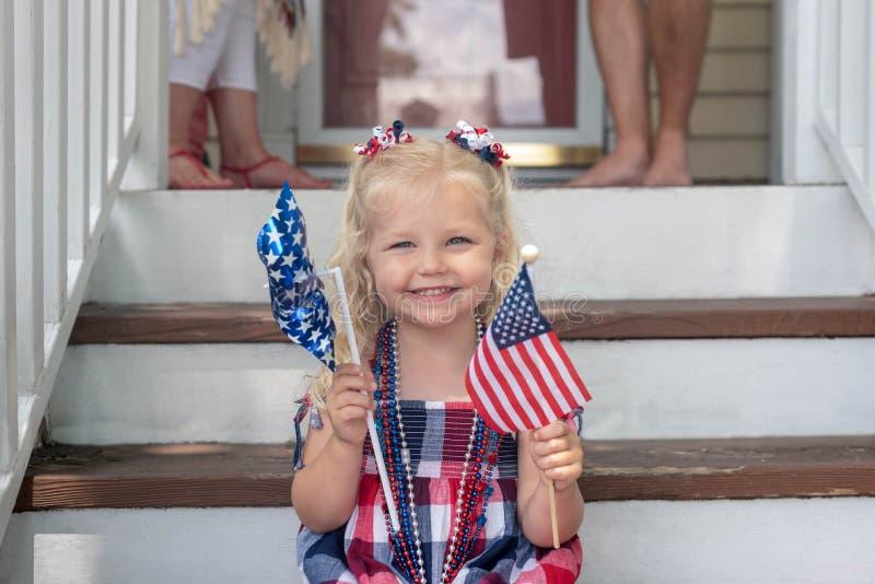Kleines Mädchen, das auf vorderen Schritten auf Viertel von Juli sitzt stockbild