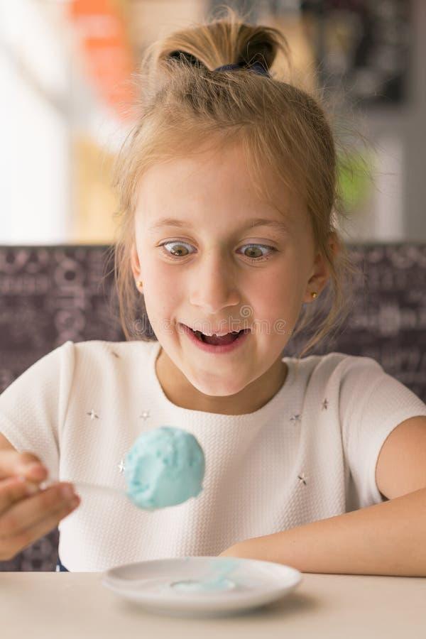 Kleines M?dchen, das blaue Eiscreme in einem Caf? isst M?dchen erfreut mit Eiscreme Entz?ckendes kleines M?dchen, das Eiscreme am stockbild