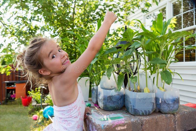 Kleines Mädchen, das Blumen in den Plastikflaschen pflanzt lizenzfreie stockbilder