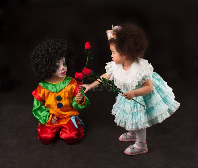 Kleines Mädchen, das Blumen kleinen Clown gibt lizenzfreie stockbilder