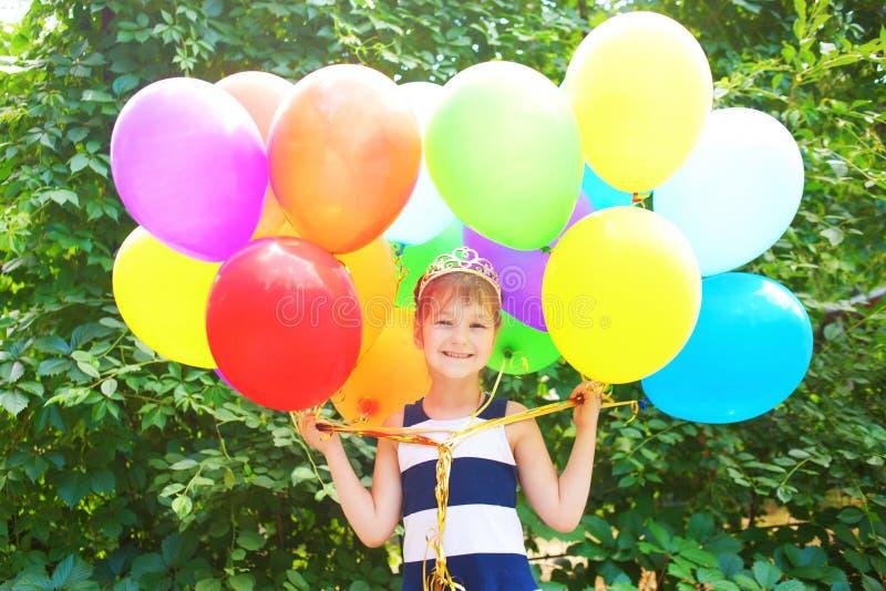 Kleines Mädchen, das bunte Ballone anhält lizenzfreie stockfotografie
