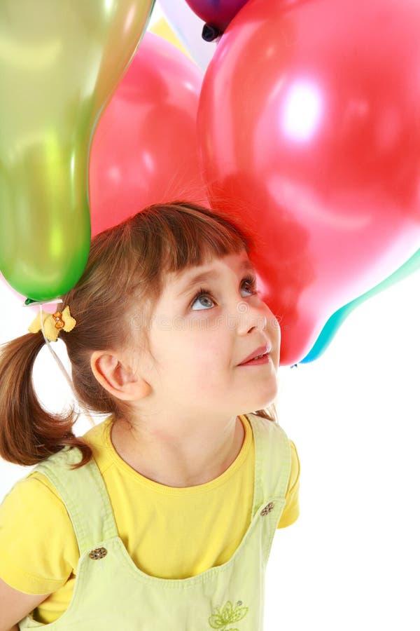 Kleines Mädchen, das bunte Ballone anhält stockfotografie