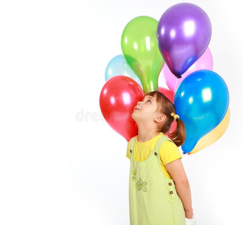 Kleines Mädchen, das bunte Ballone anhält lizenzfreies stockbild