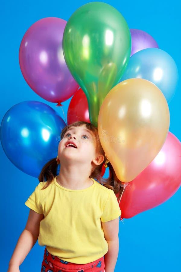 Kleines Mädchen, das bunte Ballone anhält stockfotos