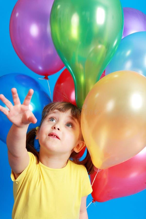Kleines Mädchen, das bunte Ballone anhält stockfoto