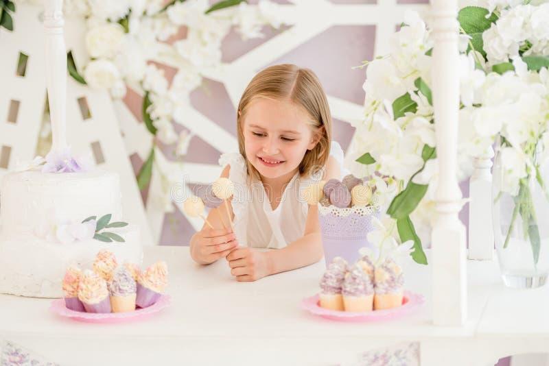 Kleines Mädchen, das bunte süße Lutscher im Schokoriegel hält lizenzfreie stockbilder