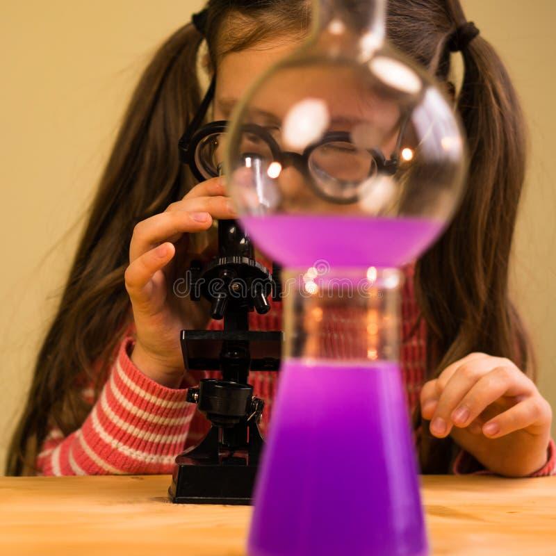 Kleines Mädchen, das chemisches Hausarbeit-Experiment mit chemischen Schiffen verarbeitet Kindererziehung lizenzfreies stockfoto