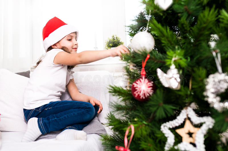 Kleines Mädchen, das christmass Baumverzierungen setzt stockbild