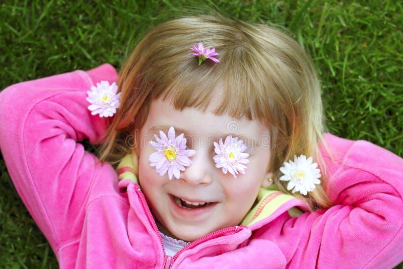 Kleines Mädchen, das daisiy Blumen des Grases in den Augen legt stockbilder