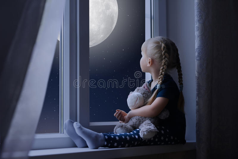 Kleines Mädchen, das den sternenklaren Himmel und den Mond betrachtet stockfoto