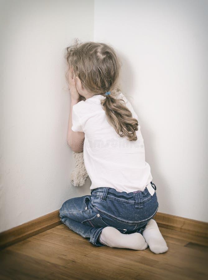 Kleines Mädchen, das in der Ecke schreit stockbild