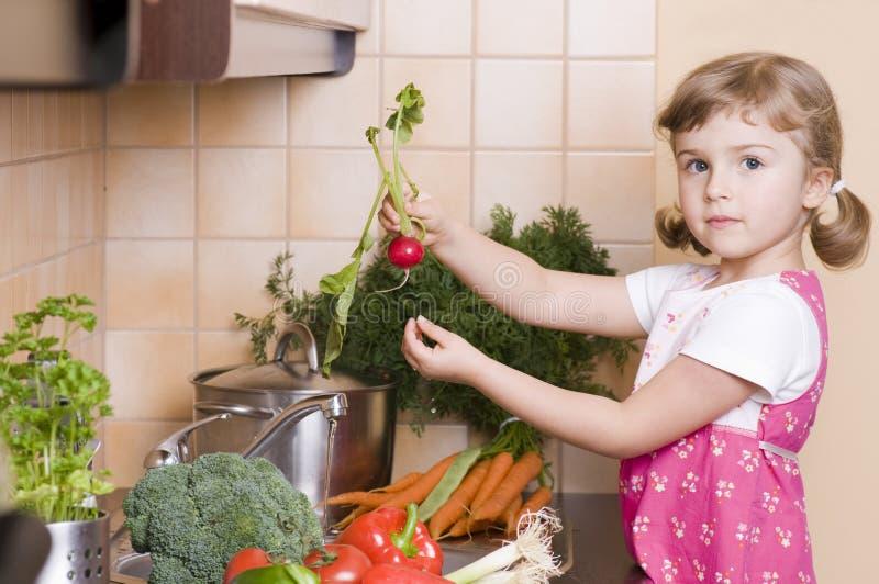 Kleines Mädchen, das in der Küche hilft lizenzfreies stockbild