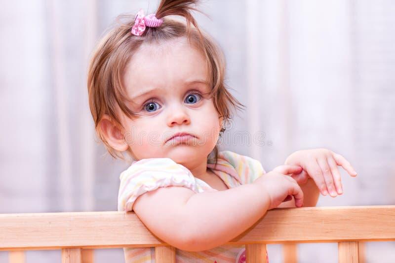 Kleines Mädchen, das in der Krippe steht stockfotografie