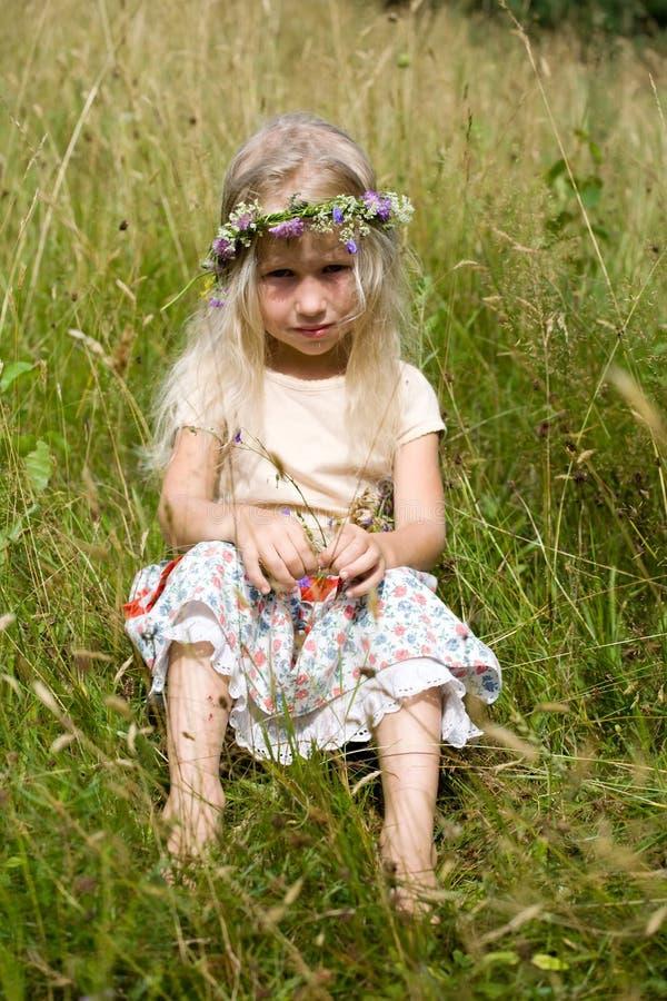 Kleines Mädchen, das an der Wiese sitzt stockfotos