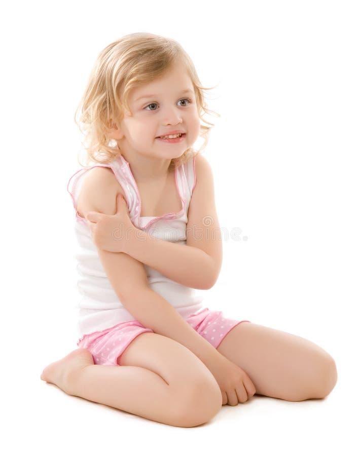 Kleines Mädchen, das die Schlafanzüge tragend sitzen auf Weiß ist stockfotos