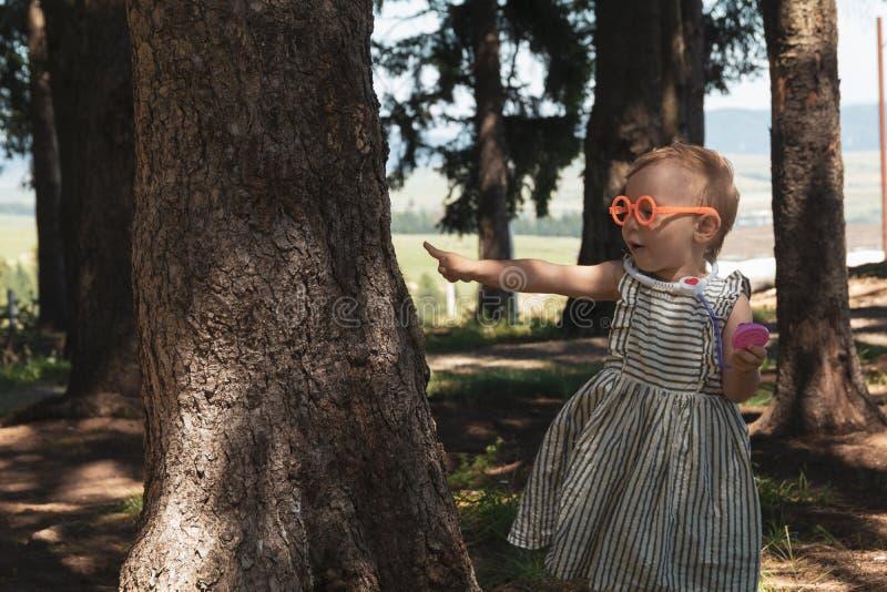 Kleines Mädchen, das Doktor mit den Bäumen in der Waldschützenden Natur spielt lizenzfreie stockfotos