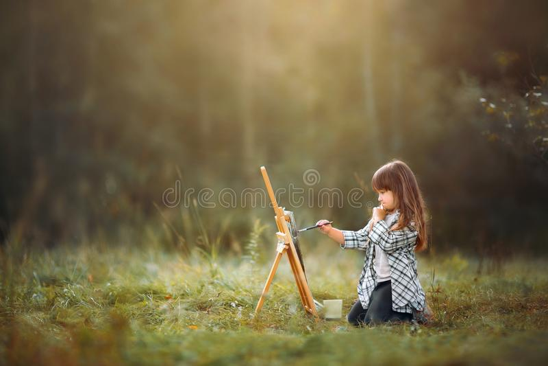 Kleines Mädchen, das draußen malt stockfoto