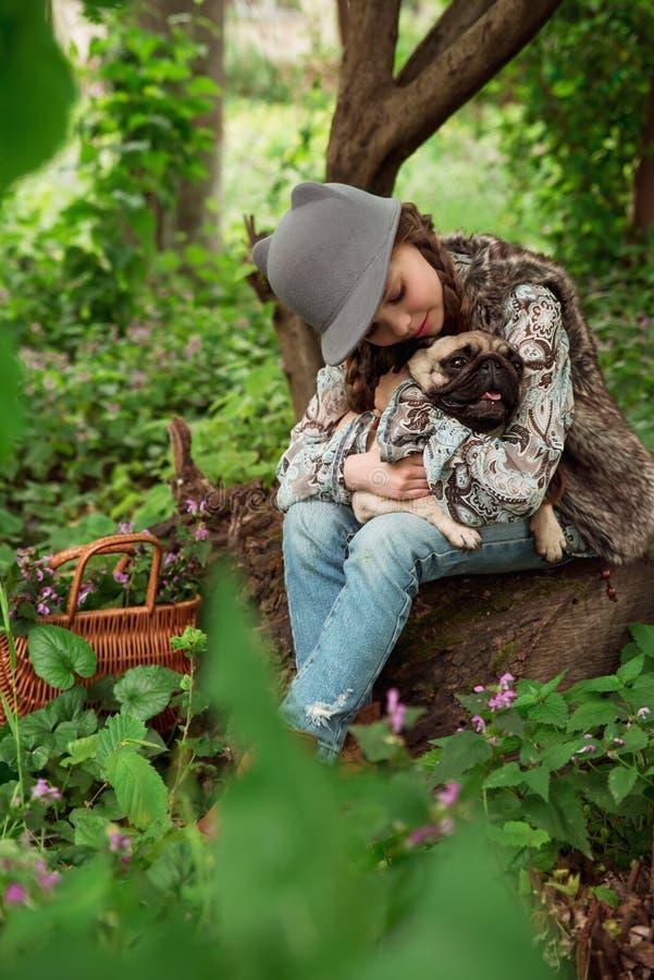 Kleines Mädchen, das draußen mit ihrem Pughund in den ländlichen Gebieten herein spielt stockfoto