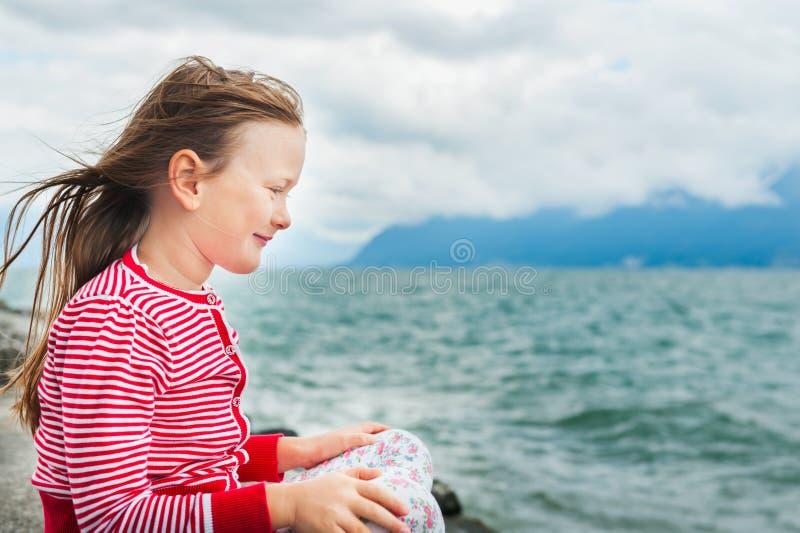 Kleines Mädchen, das durch den See an einem sehr windigen Tag stillsteht stockfotos