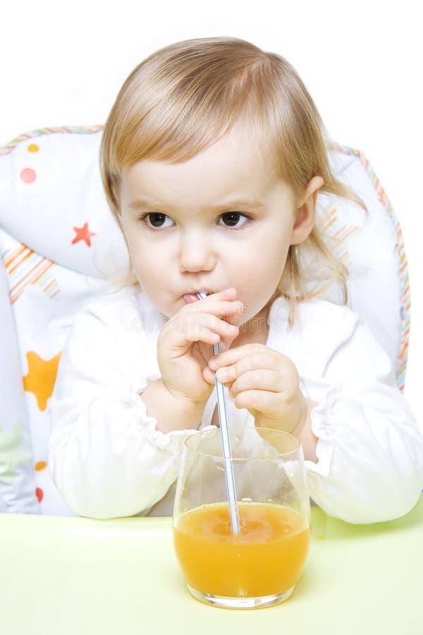 Kleines Mädchen, das durch ein Stroh trinkt lizenzfreie stockbilder