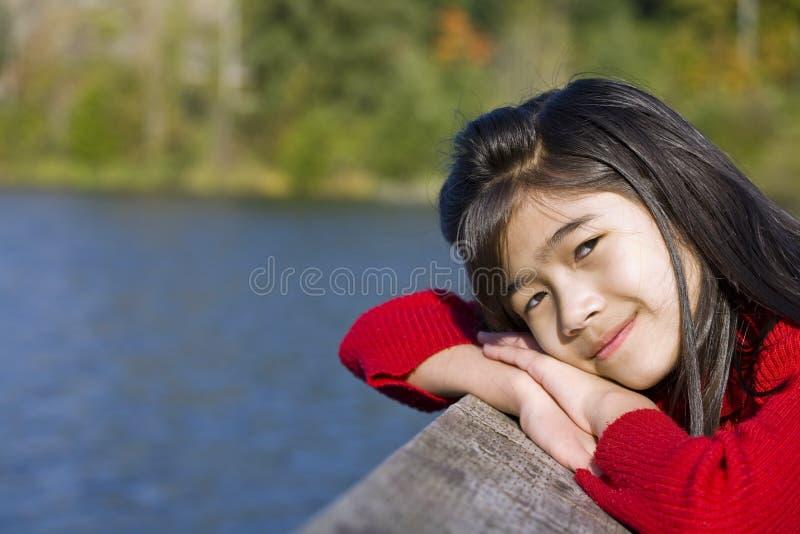 Kleines Mädchen, das durch See sich entspannt lizenzfreie stockfotografie