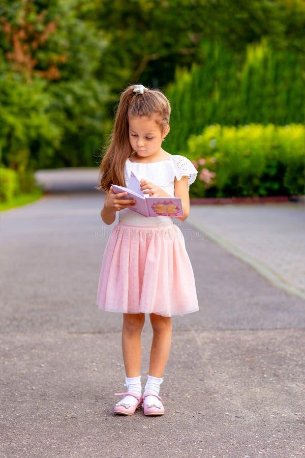 Kleines Mädchen, das ein Buch auf der Straße liest Messwert stockfotografie