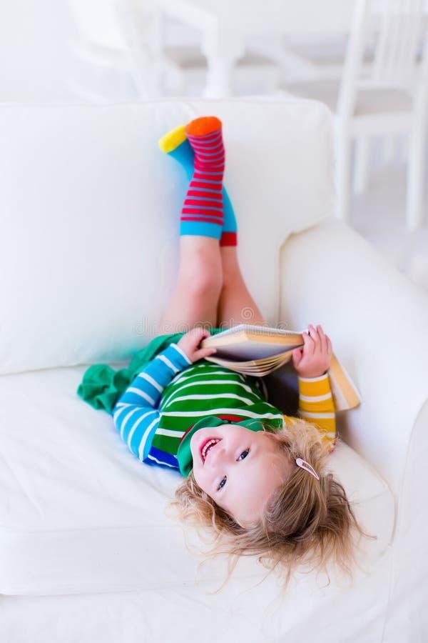 Kleines Mädchen, das ein Buch auf einer weißen Couch liest stockfotos