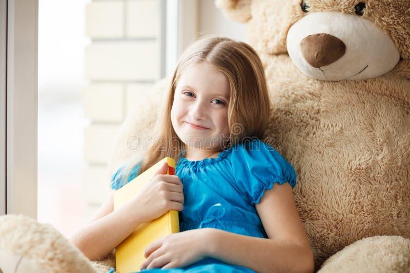 Kleines Mädchen, das ein Buch auf Fensterbrett mit großem Spielzeug hält stockfoto
