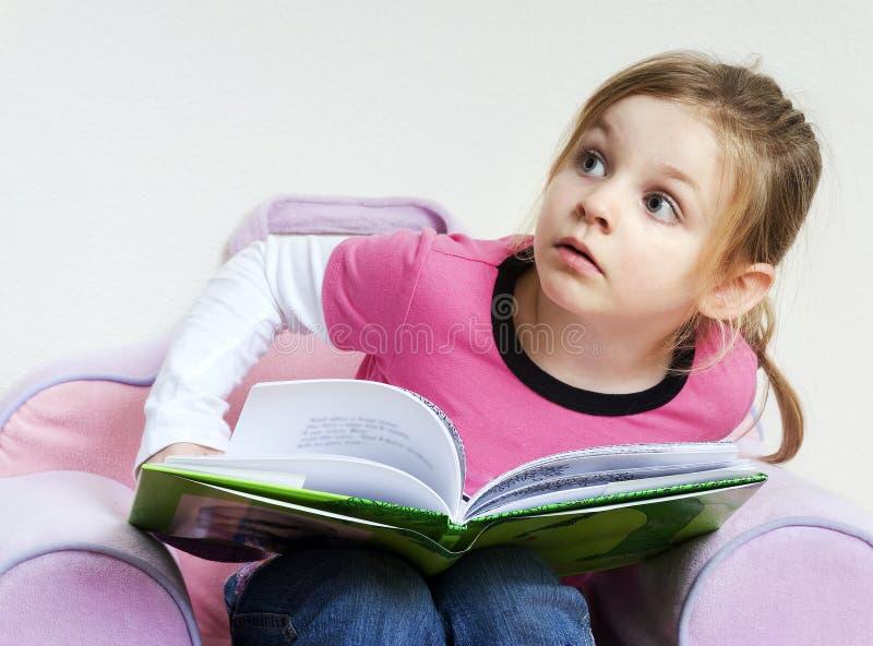 Kleines Mädchen, das ein Buch liest und oben schaut stockfotos
