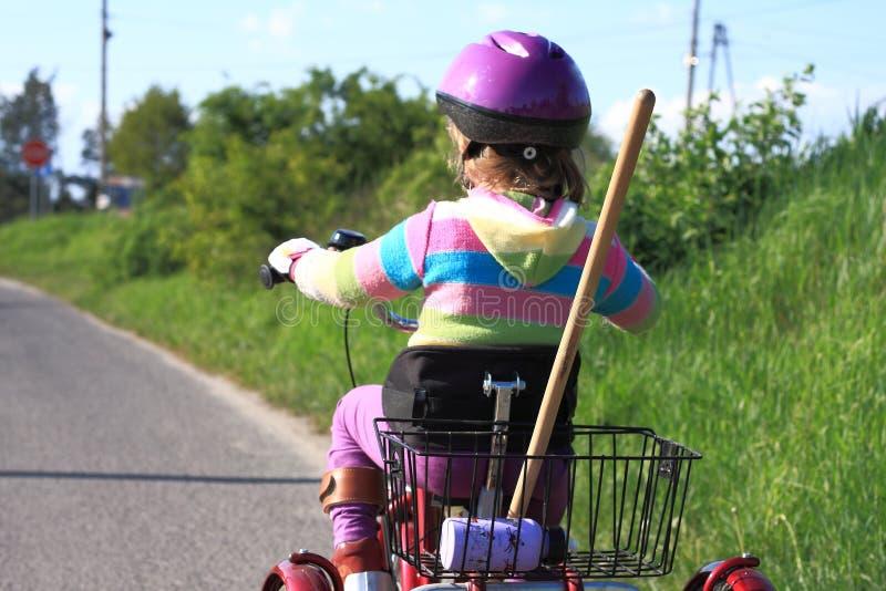 Kleines Mädchen, das ein Fahrrad mit drei Rädern reitet stockfotos