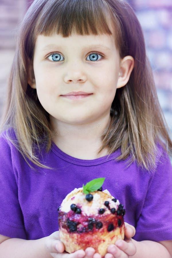 Kleines Mädchen, das ein Gebäck hält lizenzfreies stockfoto