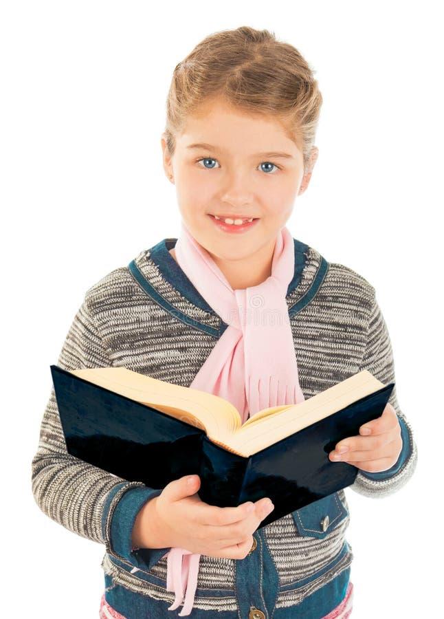 Kleines Mädchen, das ein großes Buch und ein Lächeln hält lizenzfreies stockbild