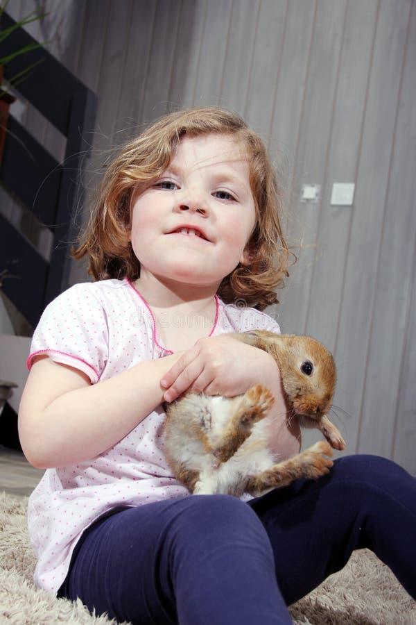 Kleines Mädchen, das ein kleines Kaninchen hält lizenzfreie stockfotografie