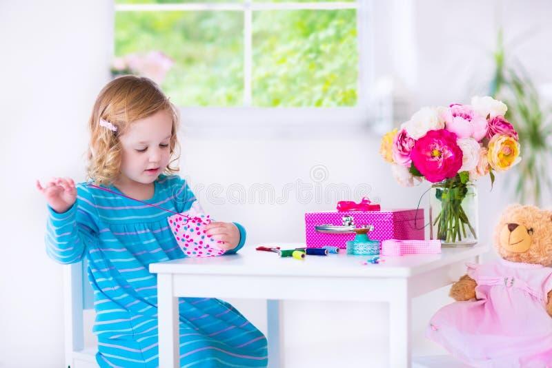 Kleines Mädchen, das ein Kleid für ihre Puppe näht stockfotos