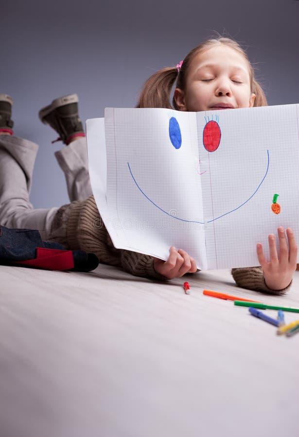 Kleines Mädchen, das ein Lächeln gezeichnet zeigt stockfoto