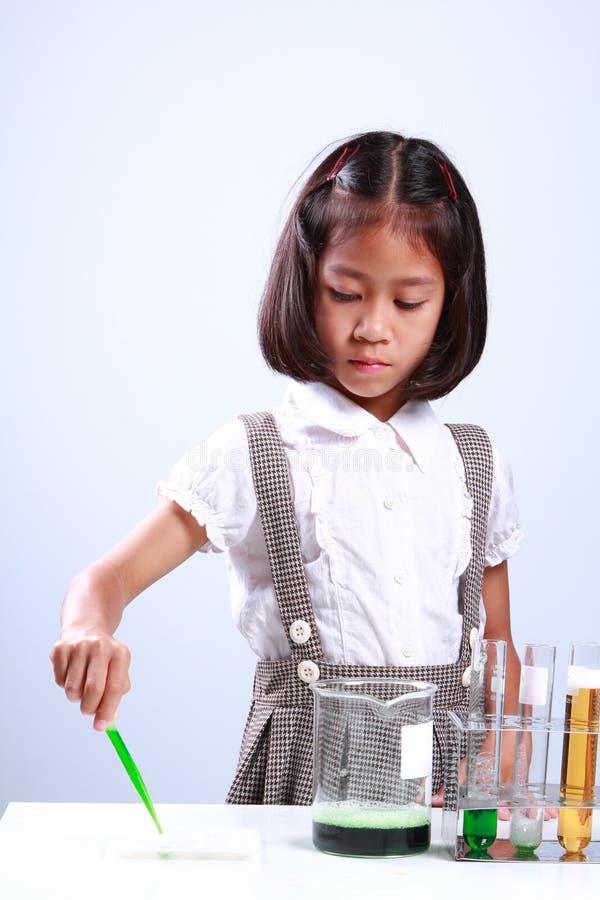 Kleines Mädchen, das ein Reagenzglas mit flüssiger Wissenschaftlerchemie und -wissenschaft hält stockfotografie
